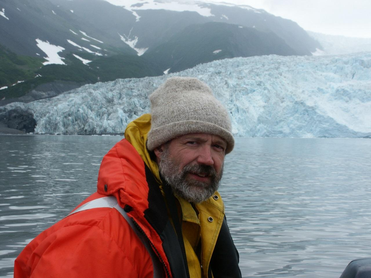 Aron Crowell photographed at Aialik Glacier on the outer coast of the Kenai Peninsula, southern Alaska in 2004. Crowell was leading archaeological fieldwork at archaeological village sites of the Sugpiaq people in Aialik Bay. Photo credit: Mark Luttrell.
