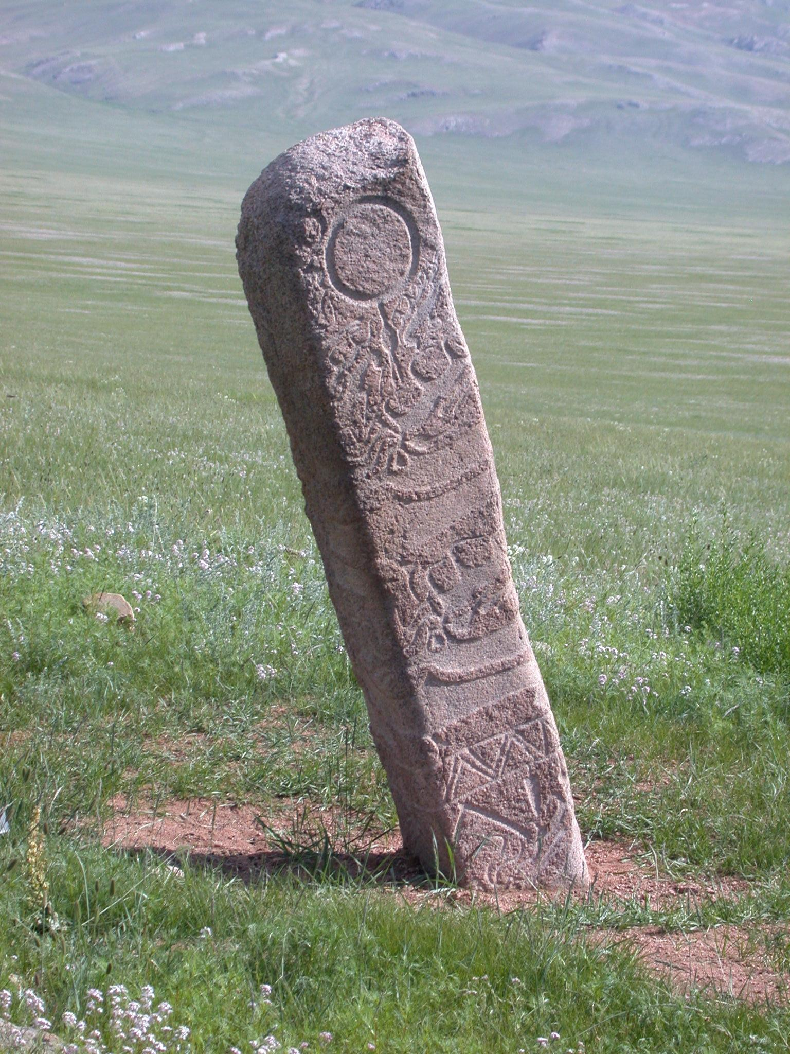 Deer Stone 5 illustrates a 'Classic Mongolian' anthropometric deer stone with its ear-ring, encircling deer-bird figures on the torso, and warrior's belt with hanging weapons. Later this site was heavily damaged by looters. Photo credit: William Fitzhugh.