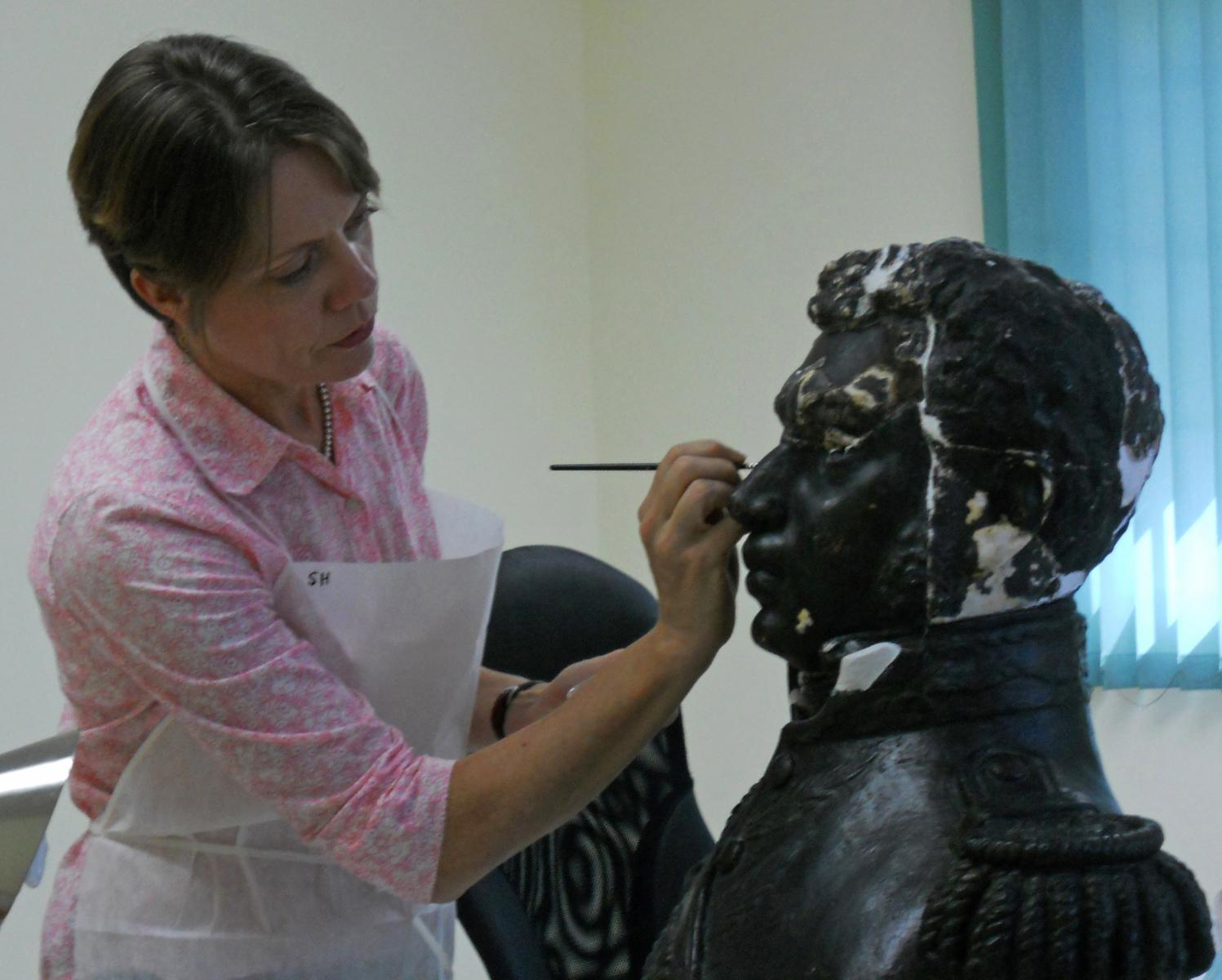 Stephanie Hornbeck inpaints a repaired plaster bust of Alexandre Pétion from the MUPANAH collection. Photo courtesy of Stephanie Hornbeck.