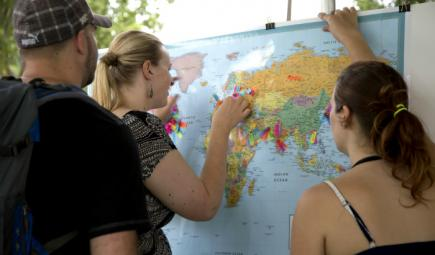 Visitors affix pins to world map indicating the languages they speak