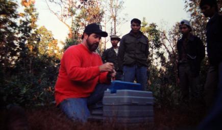 Smithsonian scientist in field preparing tracking equipment
