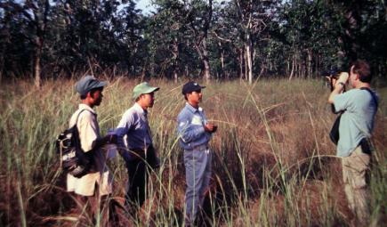Researchers look through binoculars in savannah
