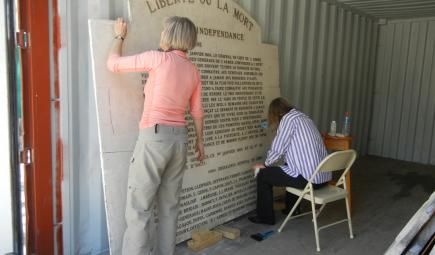 Conservators cleaning and stabilizing stone plaque