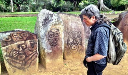Researcher at ceremonial site with Taíno symbols on stone pillars
