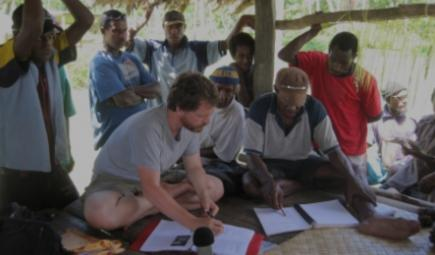 Linguist and knowledge bearer work with notebooks in open hut