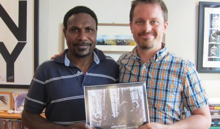 Curators holding spiral-bound translated monograph