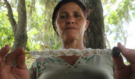 Taino healer spinning cotton from her garden