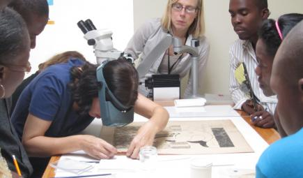 Conservator teaching workshop examining damaged paper artifact