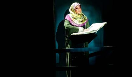 Woman in a spotlight reading to an audience in Oman