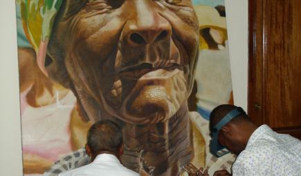 Two conservators work on mural