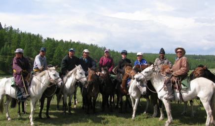 Mongolian guides with researcher on horseback