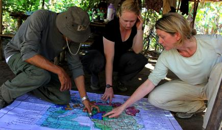 Researchers examine map and discuss land use issues in human conflict area