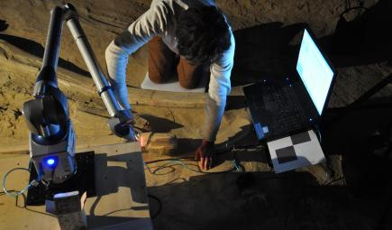 Computer and 3D scanner being used for 3D fossil modeling