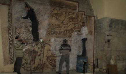 Syrians apply glue to mural wall for protection