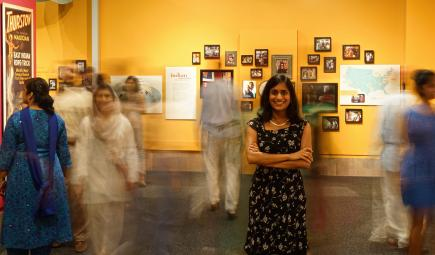 Head curator for Beyond Bollywood posing with exhibition