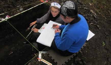 Students taking notes at archaelogical dig site