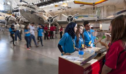 Participants in science workshop in front of airplane