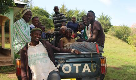 Workers at the Ngel Nyaki plot pose in back of pickup truck