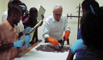 Conservator teaching workshop examining damaged object