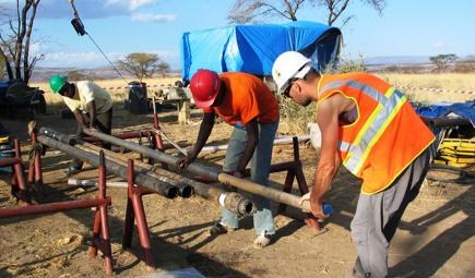 Researchers handle a segment of core drilled from Olorgesailie