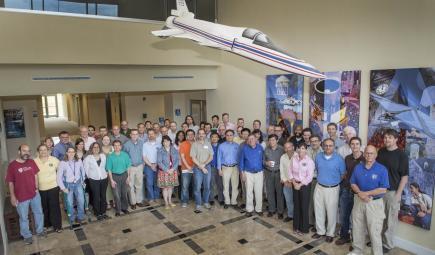 Científicos de supervisión de la contaminación atmosférica posan debajo de una nave espacial modelo