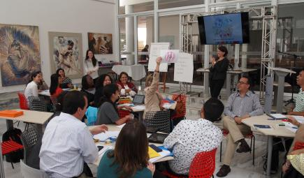 Smithsonian staff leading discussion in classroom with Brazilian participants