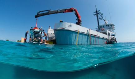 Buque de investigación bajando sumergible tripulado al agua