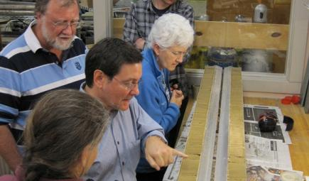 Scientific team studying split sample of core