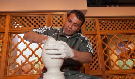 Un artiste façonne une poterie pendant l'exposition.