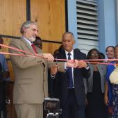 Cutting tape with dignitaries at opening of new cultural center