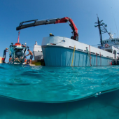 Research boat lowering manned submersible into water