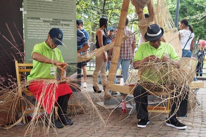 在卡利重演时,来自亚马逊地区的阿拉拉夸拉 (Araracuara) 的阿贝尔 • 罗德里格斯和奥利维利奥 • 罗德里格斯在编织他们的篮子。  照片来源:Cristina Díaz-Carrera