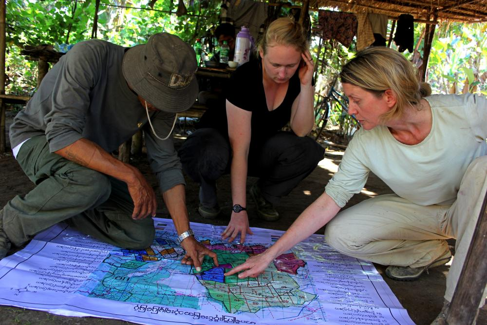 Forest Officer Than Shwe, graduate student Christie Sampson, and Mel Songer discuss land use in a high human-conflict area near the village of Thay Aye Ye in Taikkyi Township, Myanmar. Photo credit Christie Sampson.