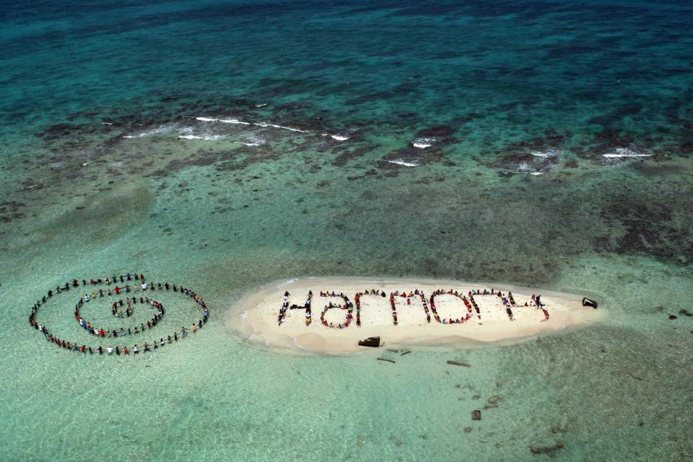 HR4HP collaborated with Spectral Q Aerial Art to create a message of hope on tiny Sergeants Caye, which is now almost fully submerged at high tide. Credit: Lou Dematteis / Spectral Q.