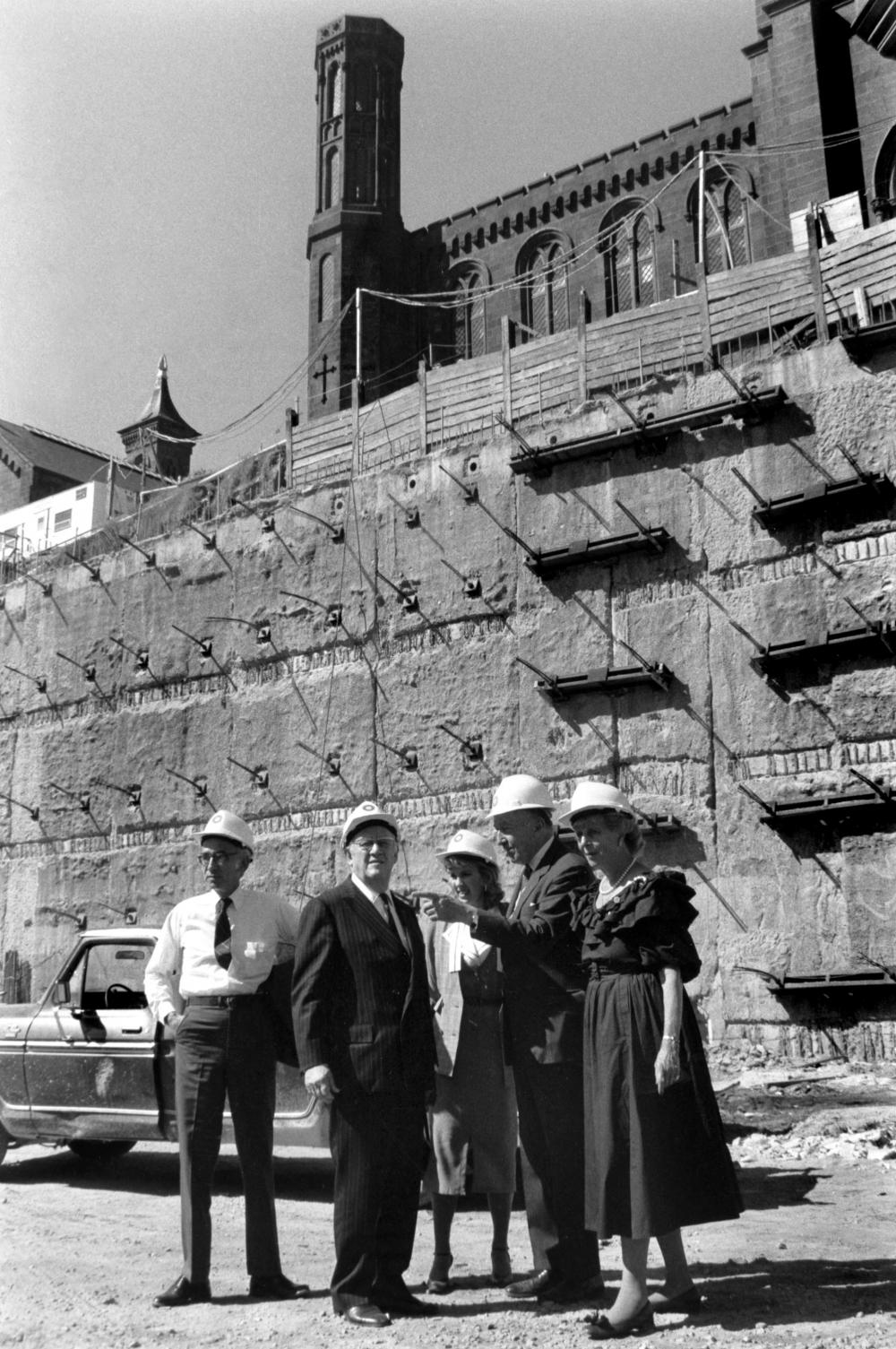 People in hard hats stand in front of construction.