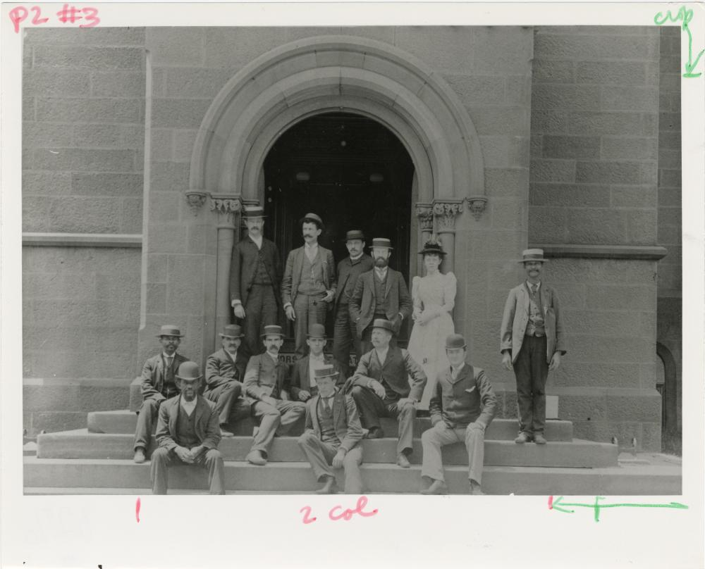 A black and white photo og a group of people in Victorian clothes standing in front of a building.