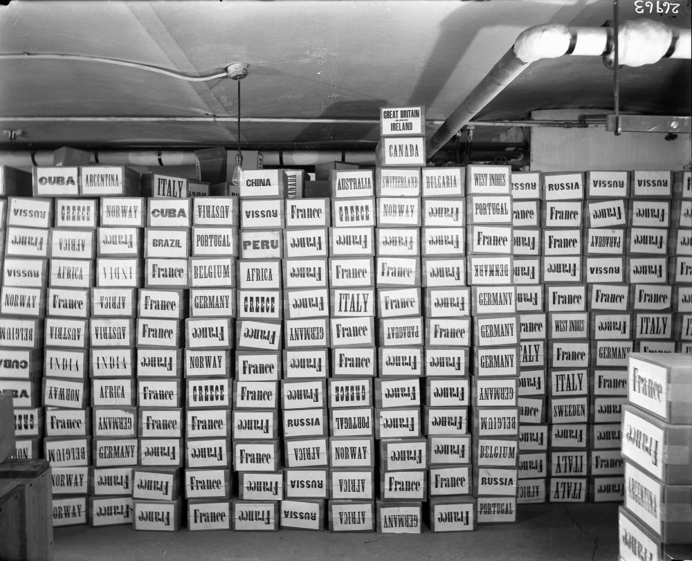 Boxes with different country names on them are stacked to the ceiling.